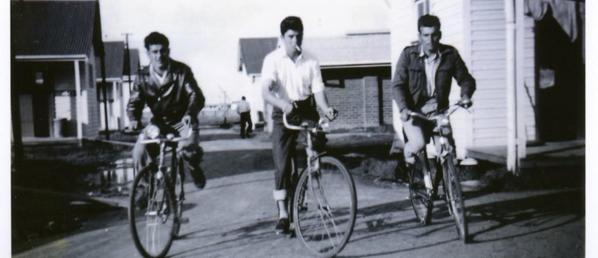 Image: three men riding bicycles between buildings