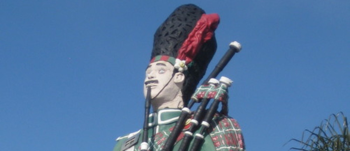 Image: large painted figure of a man in a kilt playing the bagpipes