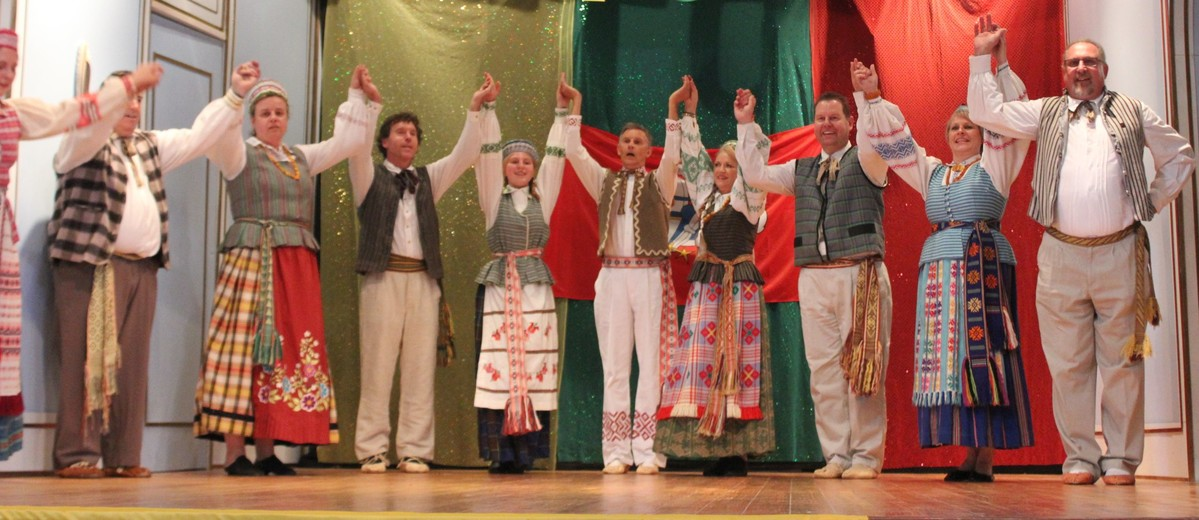 Group of people in costume on stage with large 100