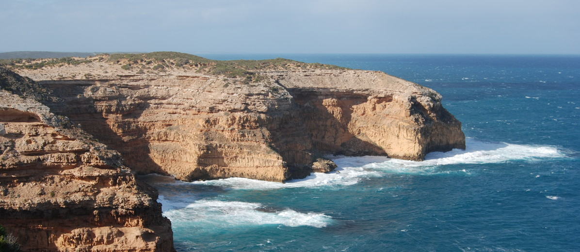 Image: A large bare cliff face juts out into the ocean