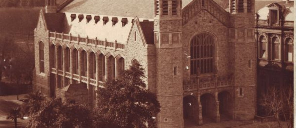 Image: a high angle photograph of a large stone hall with towers and three doors under a large window at the front.