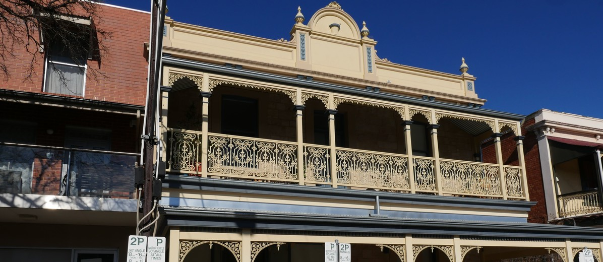 Image: two story brick building with painted ironwork and veranda