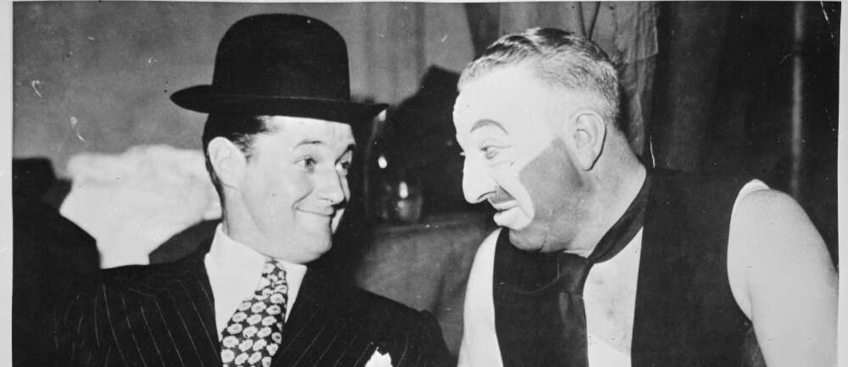 Image: Man in suit and top hat next to man in make-up and dirty vest