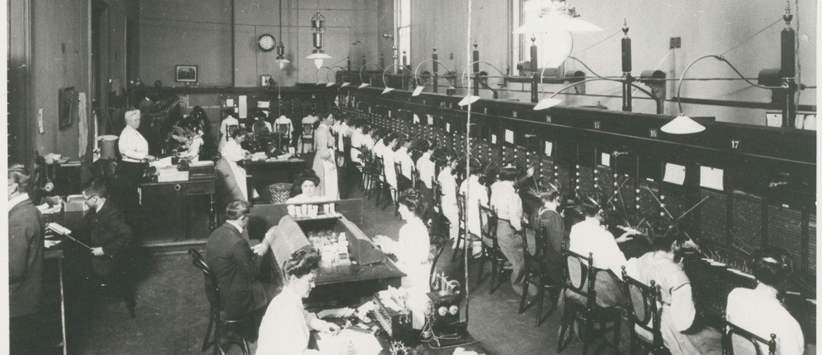 Image: A busy telephone exchange. There are rows of switchboard operators and several other staff supervising