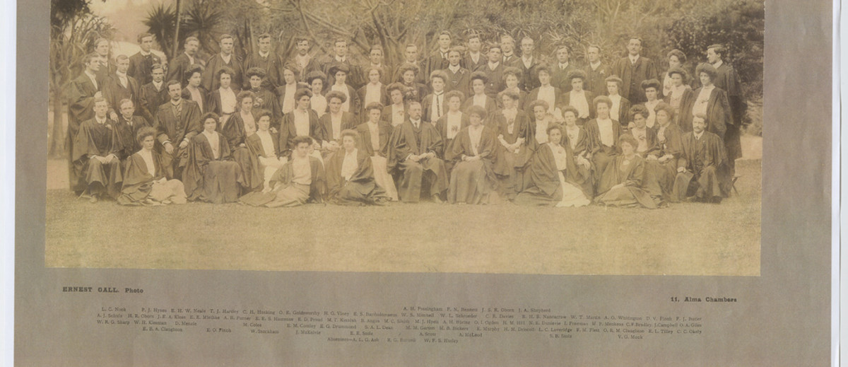 Image: A large group of Caucasian men and women in early Edwardian attire pose for a photograph in front of a stand of trees. All are wearing academic graduate gowns. A notation at the top of the photo reads: 'University Training College, 1905'