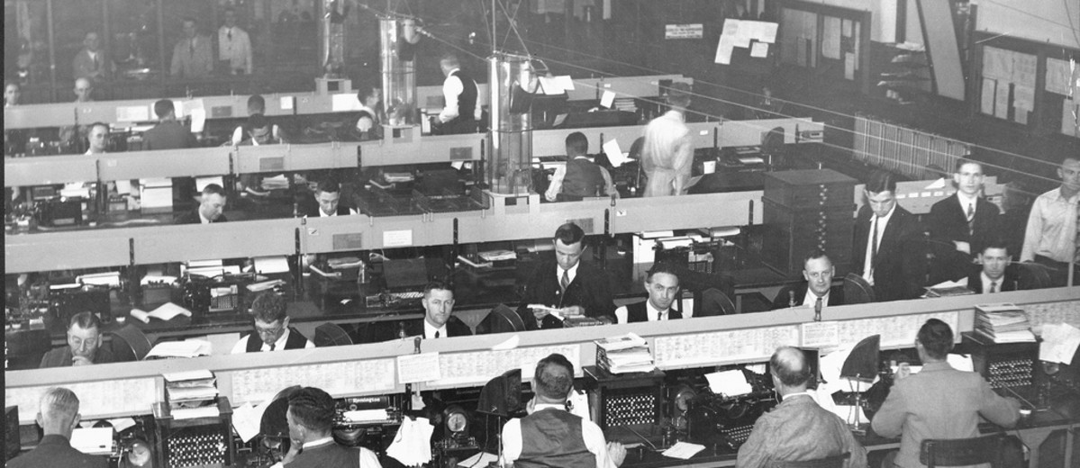 Image: The inside of a telegraph office. Men sit at rows of desks with telegraph machines