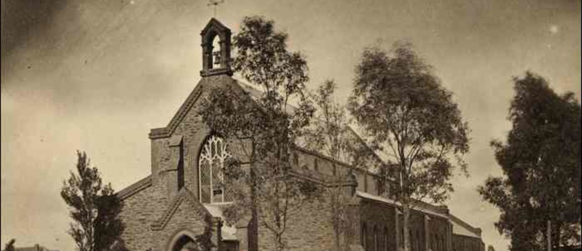 Image: A large stone church bordered by a wooden picket fence and a handful of trees. Part of a dirt street is visible in the foreground