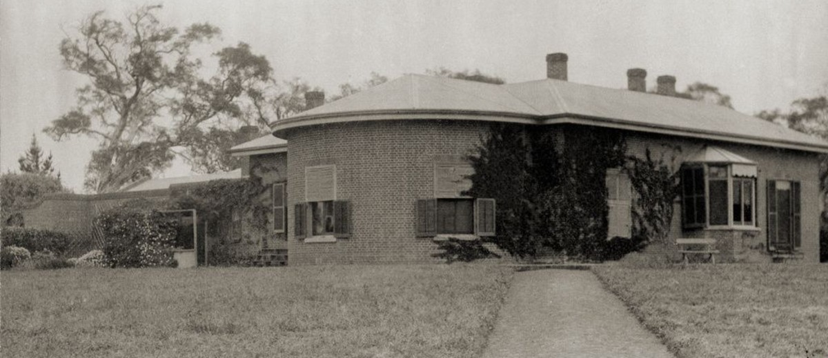 Image: A path leading through lawn to Cummins House at Novar Gardens. The house is constructed of red bricks. It has a bay windows and shutters on all windows