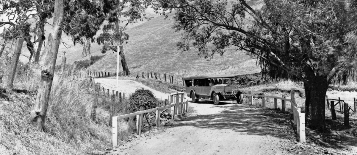 Image: A charabanc travelling along a road with fence post barriers to delineate the sharp corner for speeding motorists, 1920s.