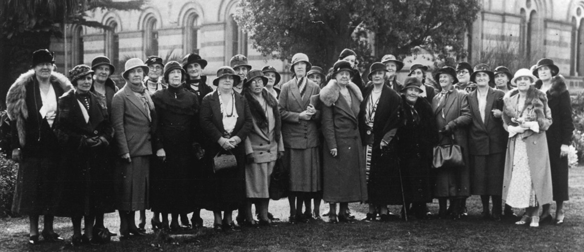 Image: A group of women standing in a line in front of two trees and a building, they all wear hats and long skirts with coats