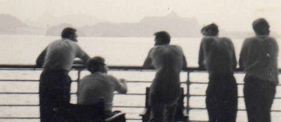 Image: silhouette of five men from behind, standing on board a ship