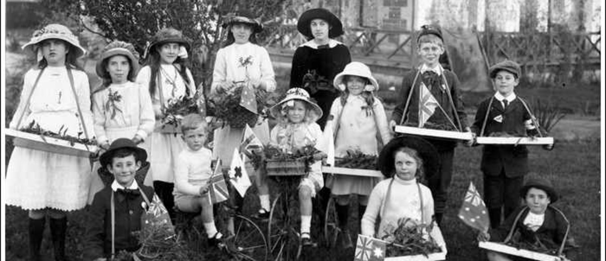 Image: A group of children stand near a house holding trays of flowers, two are on bicycles, and some are holding Australian flags