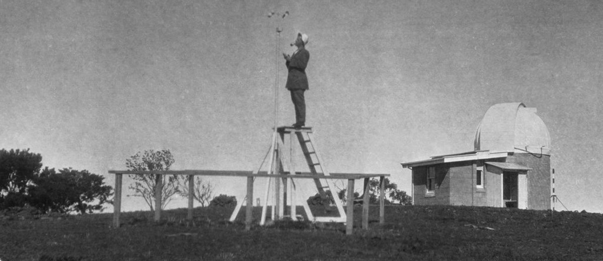 Image: A man, smoking a pipe, stands on a ladder collecting data at an outside, rural weather observatory