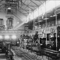 Image: a large open hall with a second storey gallery with flags hung from the railing. Rows of chairs and glass cabinets displaying various items fill the ground floor.