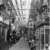 Image: A line of displays fill a large hall. In the foreground of the photograph a glass cabinet topped with a large wooden horse holds leather harnesses and other tack.