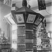 Image: a decagonal display featuring bottles of wine and spirits sits upon artfully arranged barrels. The top of the display features pictures of people and scenes. On either side of the display two others, pyramidal in shape, display similar products.