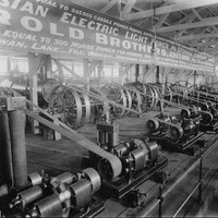 "Image: A display of 1880s ""electric light machinery"" featuring wheels and belts in a large hall."