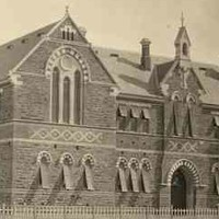 Image: a large brick building with arched windows and doors. Lighter coloured bricks are arranged in decorative diamond patterns between the first and second storeys and in an alternating pattern with the darker bricks on the arches above the windows.