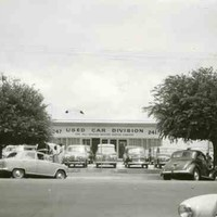 """Image: a number of 1940s and 1950s era cars are parked in rows outside a single storey building with a sign reading """"used car division"""""""