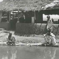 Image: Three men gather around a pool in front of a wooden framed building with a half mud-brick wall and thatched roof.