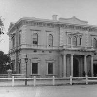 Image: Front of large, two-storey historic building with columns bordering its front door