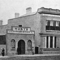 Image: a simple two storey building with an arched door to one side, a balconet and a small parapet stands next to a single storey building with a central arched door flanked by arched windows and a parapet sign reading Hunt's Labour Office