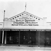 "Image: a single storey shop with a verandah and triangular parapet with a painted sign reading ""Lenroc Limited Central Service Station for Harley-Davidson, Triumph & Raleigh motor cycles & side cars"". A flag flies from the peak of the parapet."