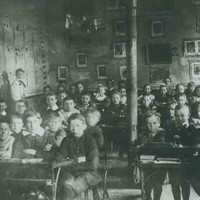 Image: a large group of boys and girls in early 20th century clothing pose sitting at their desks in a school room. In the background their teachers watch over them.