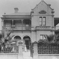 Image: A woman in a white dress and her small dog stand in front of a two storey house with a bay window, arched verandah and balconies.
