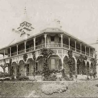 Image: Black and white photograph of two-storey stone house with wrap-around verandas on both levels