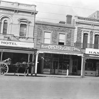 Image: a row of two and three storey commercial buildings with verandahs and/or balconies including the Crown and Sceptre Hotel, the Fish, Oyster and Grill Saloon, A.F. Shelton's Ham Shop and the King's Theatre.
