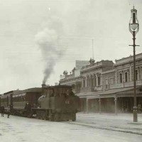 Image: passengers board a steam train which is stopped in the middle of a city street