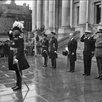 Image: a small group of men in military dress uniforms stand saluting on the pavement in front of a set of stone steps leading up to a building with columns.