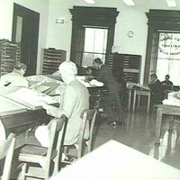 Image: Men sitting at tables reading newspapers in a large room