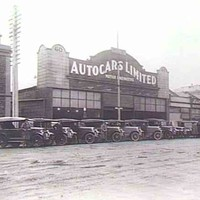 "Image: a row of 1920s era cars are parked on a 45 degree angle facing a dirt road. Behind them is a single storey commercial building, part of a row of terraced shops, with a curved parapet and a sign which reads ""Autocars Limited""."