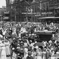 "Image: a huge crowd of men, women and children in early 20th century dress gather in a city street in celebration. Written on the photograph are the words ""King William St, Adelaide: 12.11.18"""