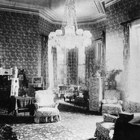 Image: late 19th century drawing room with high ceilings, a large chandeleir and heavily-patterned wallpaper and furniture
