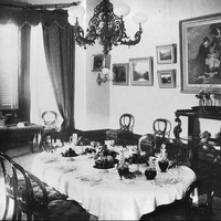Image: The dining room of a large house in the 1890s. The room has a number of paintings on the wall, a bay window, and the table is set for eight.