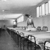 Image: a woman in a nurses uniform makes a bed halfway down a long row of beds. A second row lines the opposite wall.