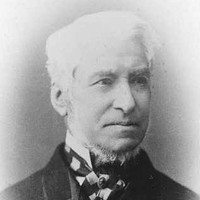 Image: a head and shoulders portrait of a man with white hair and a thin beard under his chin, his chin itself being shaven. He wears a dark coat and a striped cravat.