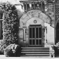 Image: Front entrance to large stone house. Stone steps lead up to the arched front door, flanked by two columns. To the left a window is completely surrounded by ivy and to the right is a verandah with decorative wooden fretwork.