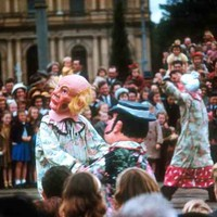 Image: a number of clowns parade past a crowd with a large number of children as part of a Christmas pageant