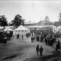 Image: a crowd of men and women in early 1870s clothing stand amongst tents and agricultural displays. In the background a large building can be seen.