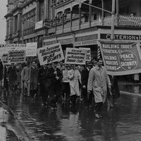 Image: men in 1940s era clothing march through the rain holding protest signs demanding increased rights for workers