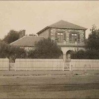 Image: a two storey stone house behind a high fence and partly obscured by trees. The second story windows are shuttered and an arched verandah supports a balcony with stone balustrade.