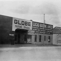 "Image: a man in a 1930s era coat poses on a motorcycle outside a shop with a rectangular arched entrance and sign reading ""Globe Motor Park"""