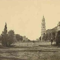 Image: a black and white photograph of a view across a city park and down a wide dirt street. Lining the street are a number of large public buildings including one with a large tower.