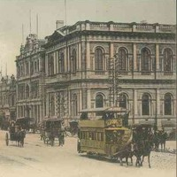 Image: horse drawn buses and carts travel down a busy city street lined with large commercial buildings