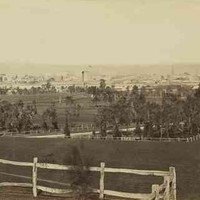 Image: the view of a small city from behind a low wooden fence atop a small hill.