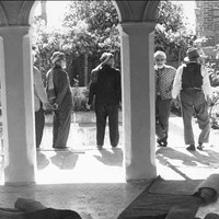 Image: Five Afghan men stand in the courtyard of a building. Two ornate columns are visible in the foreground